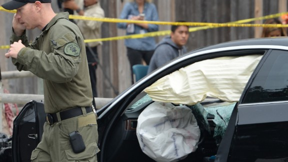 An investigator speaks on a cell phone while examining the gunman