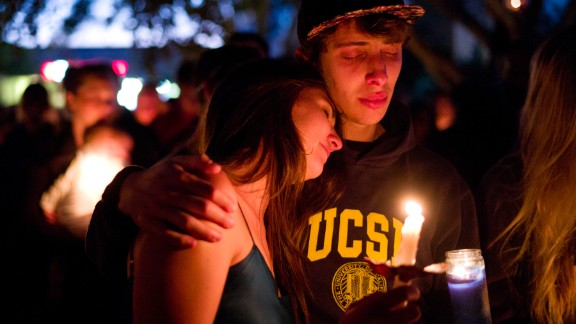 Two students comfort each other during the candlelight vigil to honor the victims of Friday night