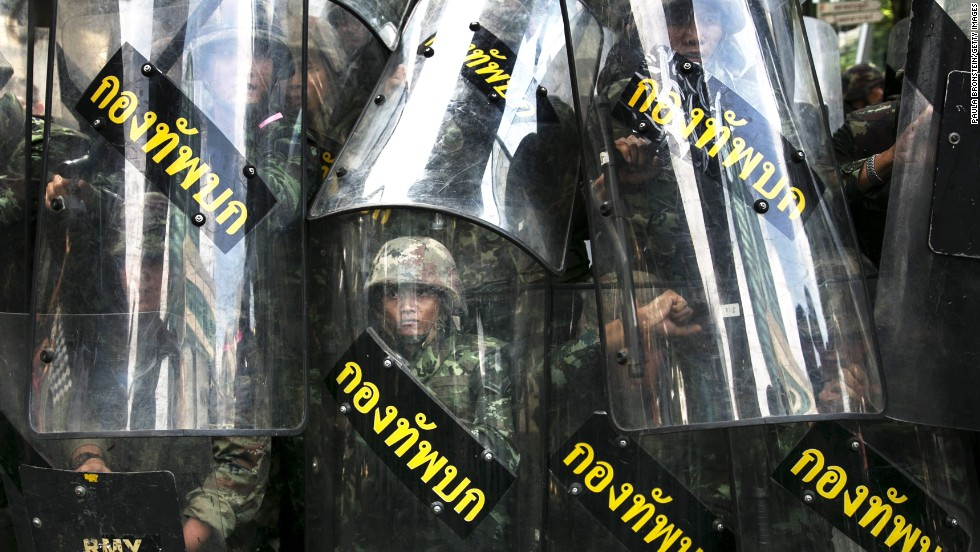 Thai soldiers stand behind their riot shields as protesters threaten them May 25 in Bangkok.