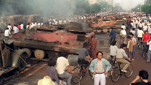 BEIJING, CHINA: Beijing residents inspect the interior of some of over 20 armoured personnel carrier burnt by demonstrators to prevent the troops from moving into Tiananmen Square 04 June 1989. On the night of 03 and 04 June 1989, Tiananmen Square sheltered the last pro-democracy supporters. Chinese troops forcibly marched on the square to end a weeks-long occupation by student protestors, using lethal force to remove opposition it encountered along the way. Hundreds of demonstrators were killed in the crackdown as tanks rolled into the environs of the square. (Photo credit should read MANUEL CENETA/AFP/Getty Images)