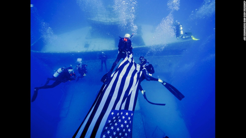 Divers deploy an American flag on the USNS General Hoyt S. Vandenberg, an artificial reef about seven miles off Key West, Florida, on May 25, 2014.
