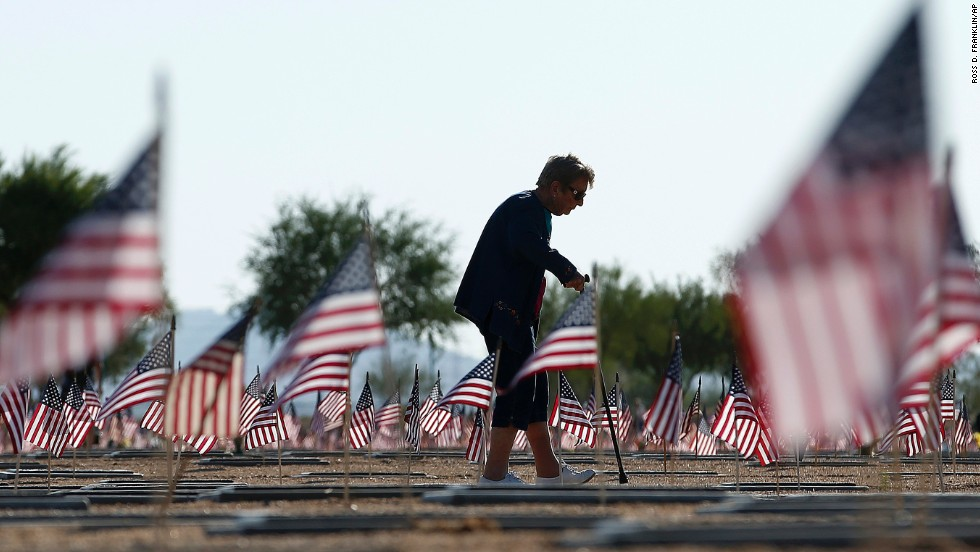 After visiting the grave of her husband, World War II veteran William Murphy, Raymonde Murphy walks past graves at the National Memorial Cemetery of Arizona in Phoenix on May 26, 2014.