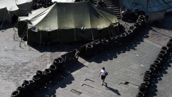 A woman walks May 26 near barricades built by protesters in Kiev