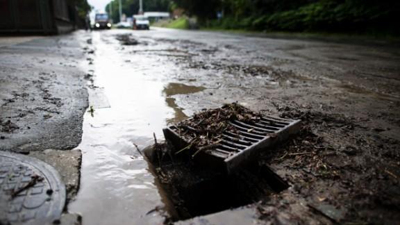 [File] An open sewage drain following heavy rains in Visé on June 21, 2013.