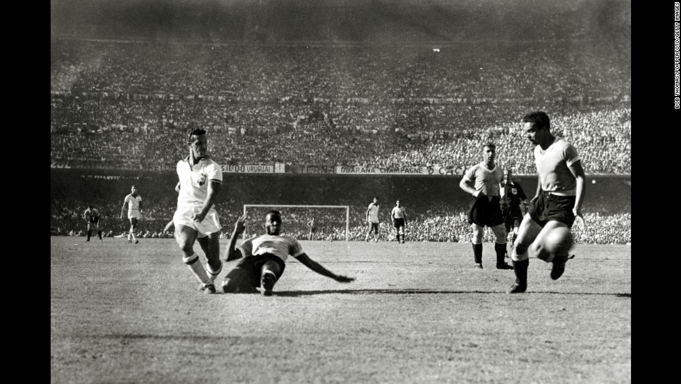 Ademir is challenged by Uruguayan defender Rodriguez Andrade as he shoots a shot wide. There were nearly 200,000 people watching the match at the Maracana Stadium.