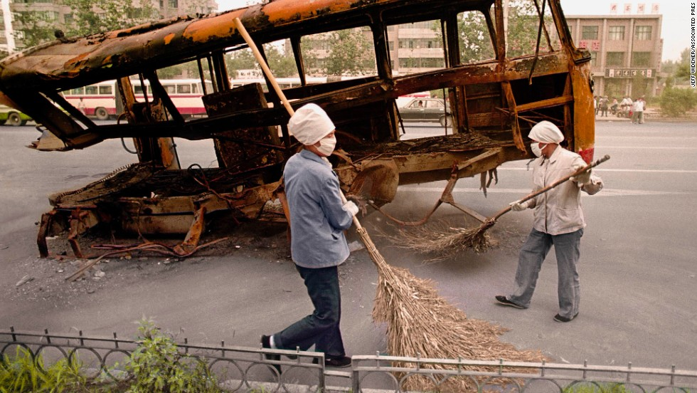 "Street sweepers on the morning after the June 4 crackdown. Widener went back to China on the 20th anniversary of the tragedy in 2009: ""What I saw was a happier China. There was an incredible amount of department stores. When the lights were blazing at night, some places looked like Las Vegas. I stayed at the Jianguo hotel for nostalgic reasons. Nothing there had changed, except the staff were much, much friendlier."""