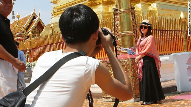 Caption:CHIANG MAI, THAILAND - APRIL 17: Chinese tourists take pictures at Wat Pra That Doi Suthep on April 17, 2014 in Chiang Mai, Thailand. Due to a rapidly growing economy, more than 100 million mainland Chinese are expected to go abroad this year. In Chiang Mai, which is seeing a surge in Chinese tourism after a popular Chinese movie was set there with a recent poll finding that 80% of residents were displeased with Chinese behavior while abroad. (Photo by Taylor Weidman/Getty Images)
