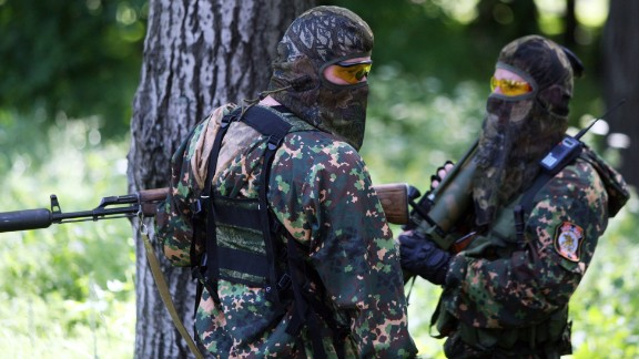 Pro-Russian militants armed with an assault rifle and a rocket launcher stand during combat with Ukrainian troops at the international airport of the eastern Ukrainian city of Donetsk on May 26, 2014.