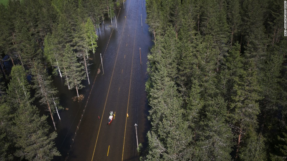 Two men paddle in a canoe on a flooded road in Trysil, Norway, on Monday, May 26. Rain and melted snow have increased the water level of the river Trysilelva.