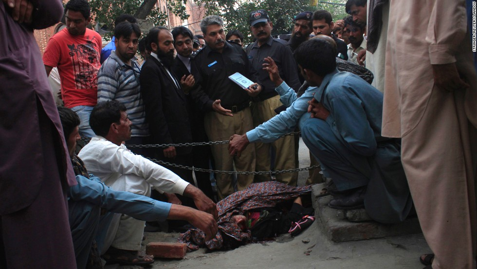 "Police collect evidence near the body of <a href=""http://www.cnn.com/2014/05/28/world/asia/pakistan-pregnant-woman-killed/index.html"">Farzana Parveen</a>, who they say was killed by her relatives near the Lahore High Court building in Lahore, Pakistan, on Tuesday, May 27. Parveen, 25, was beaten to death with bricks because she had eloped with the man she loved rather than marry the man chosen by her family."