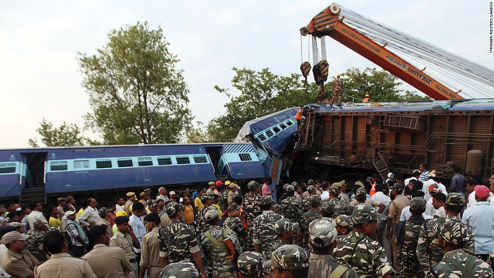 Security personnel and rescue team members stand next to a damaged passenger train that derailed in Khalilabad, India, on Monday, May 26. At least 40 people were killed and more than 150 were injured after the train collided with a stationary cargo train, police and railway officials said.