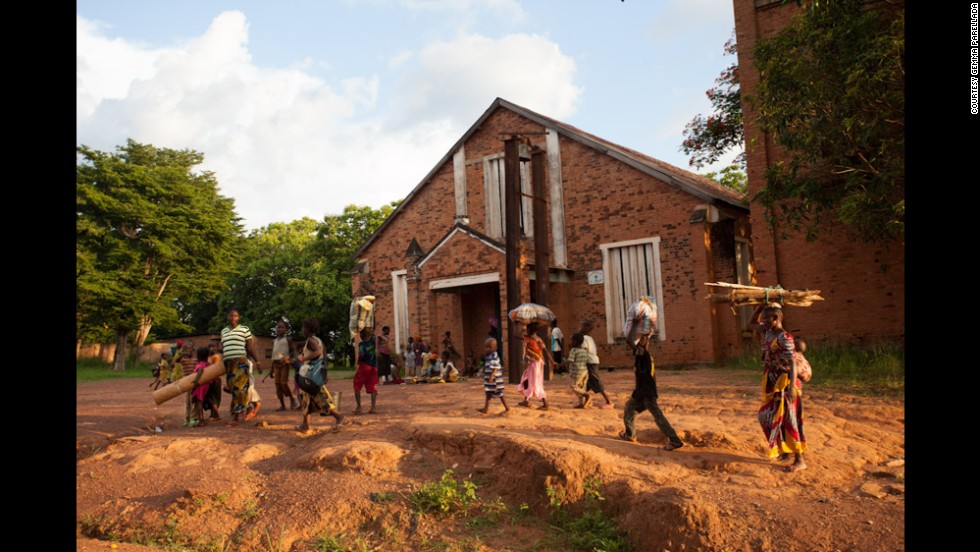 Families pass the cathedral in Bambari and look for safety following the clashes between Muslim youths and peacekeepers. For three days, the two sides fought for control of the one bridge into town.