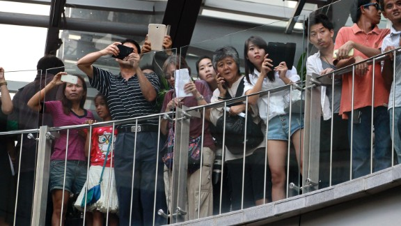 """Onlookers at a Bangkok shopping mall watch as protesters shout  """"Freedom!"""" and """"Democracy!"""" on June 1."""