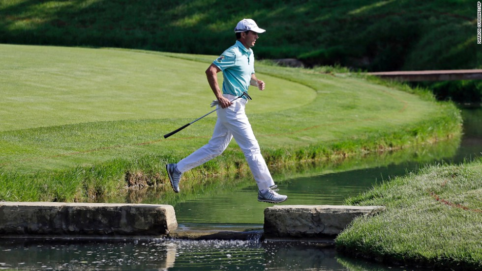 Golfer Mike Weir runs hops over a water hazard Friday, May 30, during the second round of the Memorial Tournament in Dublin, Ohio. Weir missed the cut of the event, which was won by Hideki Matsuyama in a playoff.