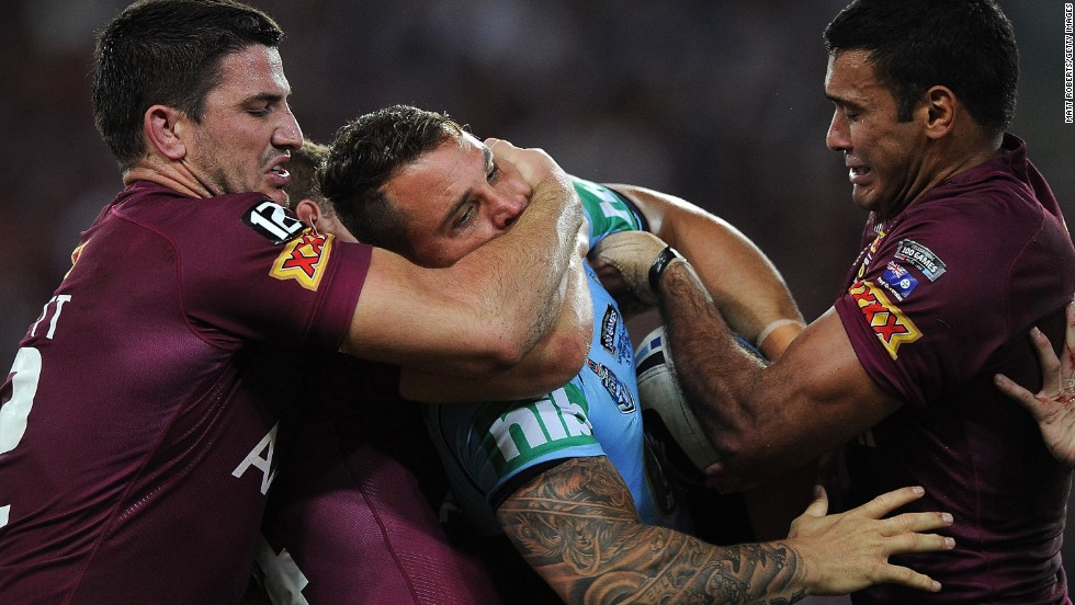 Anthony Watmough of the New South Wales Blues is tackled by two players of the Queensland Maroons during Game 1 of the State of Origin series, which was played Wednesday, May 28, in Brisbane, Australia. The Blues won the rugby league game 12-8, and the two teams will continue the best-of-three series on June 18.