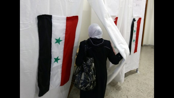 The Syrian flag is seen hanging on a polling booth as a woman goes to cast her ballot in the Syrian presidential election Tuesday, June 3, in Damascus, Syria. The election took place while civil war still rages in the country, and only in areas controlled by the regime of current President Bashar al-Assad.