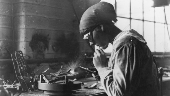 A female munitions worker welds at an armaments factory.