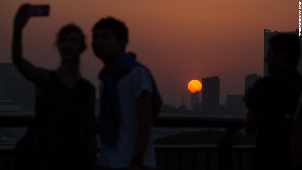 Two people take a selfie as the sun sets over the Tokyo skyline on Saturday, May 31.