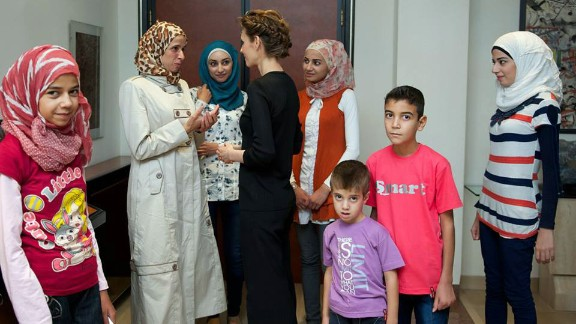 A photo on the Syrian Presidency Facebook page of Asma al-Assad with relatives of martyrs in Damascus on October 1, 2013.