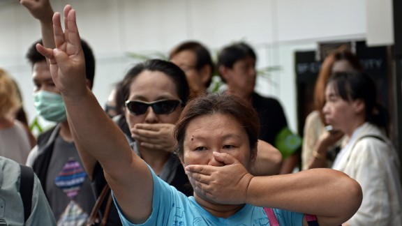 """(FILES) This file picture taken on June 1, 2014 shows anti-coup protesters flashing a three-finger salute during a gathering at a shopping mall which was broken up by security forces in downtown Bangkok. Opponents of Thailand's military coup are risking arrest by flashing the three-finger salute from the """"Hunger Games"""" movies to defy a junta that has banned all public protests. The gesture has become the unofficial symbol of resistance against a military regime that has suspended democracy and severely curtailed freedom of expression. AFP PHOTO / FILES / Christophe ARCHAMBAULTCHRISTOPHE ARCHAMBAULT/AFP/Getty Images"""