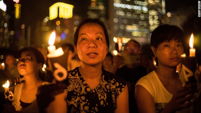 People take part in a candlelight vigil on the 25th anniversary of the Tiananmen Square protests during heavy rain on June 4, 2014 in Hong Kong.