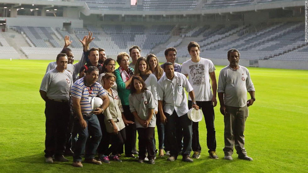 President Rousseff poses with workers as she visits Arena da Baixada stadium on May 9, 2014, which will host four matches of the upcoming FIFA World Cup Brazil 2014, in Curitiba, Brazil.