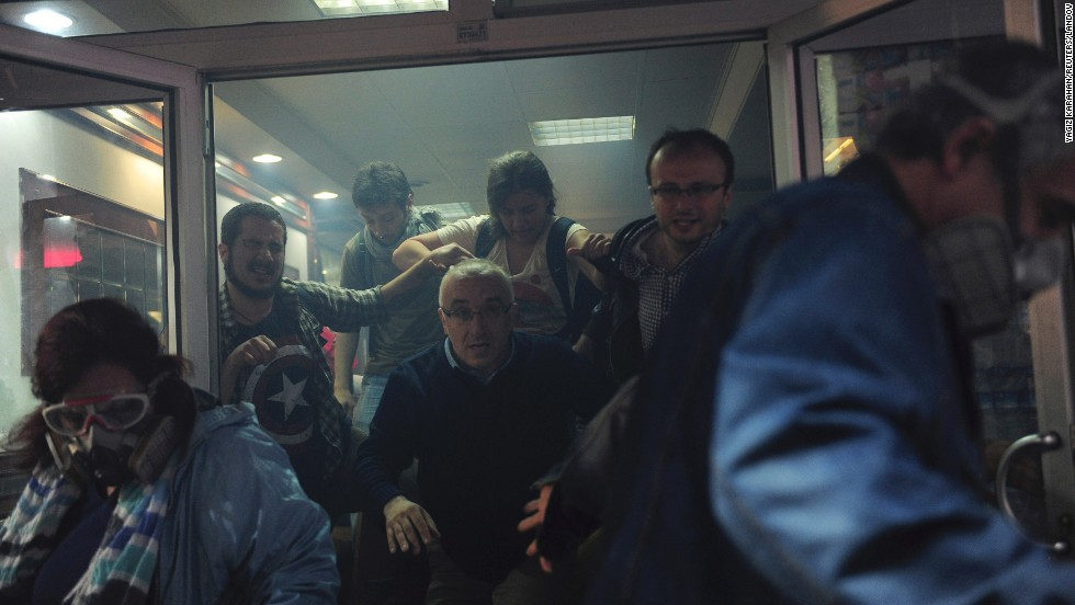 "People try to escape from an Istanbul cafe after tear gas seeped into the building on Saturday, May 31. Outside, police fired tear gas and water cannons to disperse demonstrators looking to mark the <a href=""http://www.cnn.com/2014/05/31/world/europe/turkey-cnn-reporter-harassed/index.html"">one-year anniversary of mass protests</a> in the Turkish capital."
