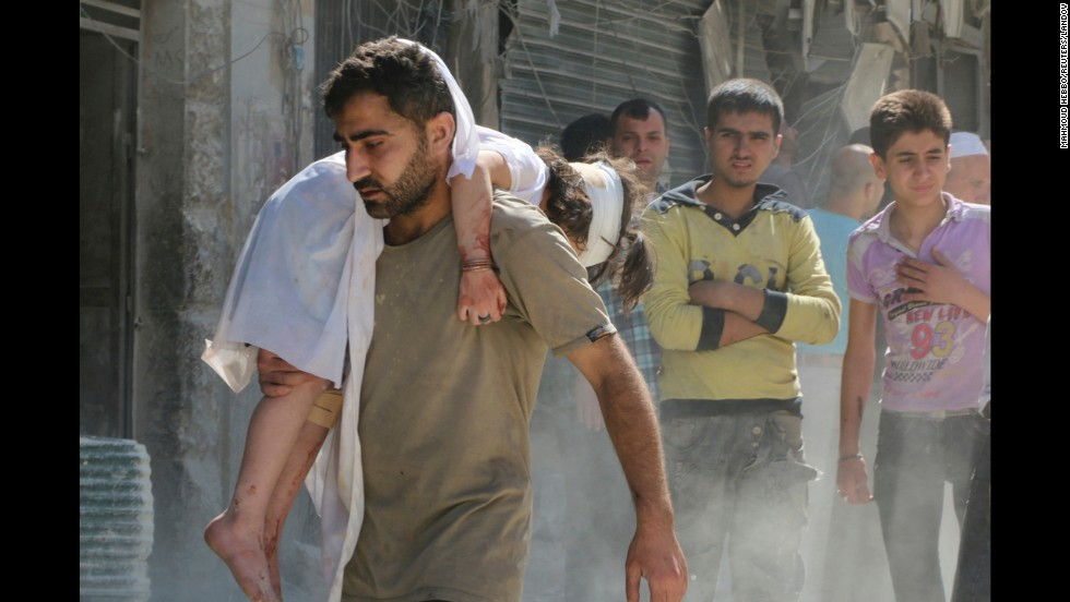 "A man in Aleppo, Syria, holds an injured child at a site that activists say was bombed Tuesday, June 3, by forces loyal to Syrian President Bashar al-Assad. Civil war <a href=""http://www.cnn.com/2014/02/10/middleeast/gallery/syria-unrest-2014/index.html"">still rages in the country</a> more than three years after an uprising in March 2011."