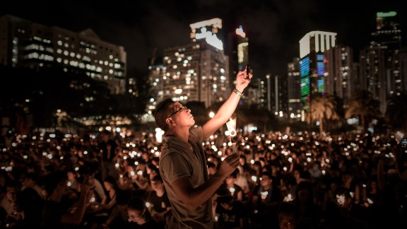 A man takes a picture with his mobile phone as people hold candles to commemorate China's 1989 Tiananmen Square events during a candlelight vigil in Hong Kong on June 4, 2014. Up to 200,000 people were set to take part in a candlelight vigil in Hong Kong on June 4 to commemorate the 25th anniversary of the bloody Tiananmen Square crackdown, as China seeks to wipe the incident from memory.
