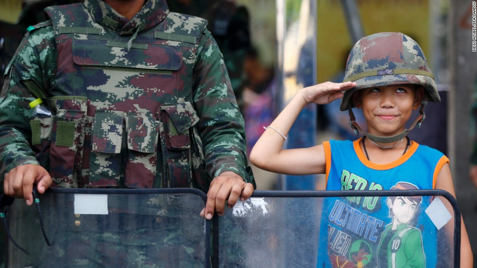"A young boy wearing a military helmet poses with Thai soldiers as they block a road to prevent protests Friday, May 30, in Bangkok, Thailand. The Thai military <a href=""http://www.cnn.com/2014/05/19/asia/gallery/thailand-crisis/index.html"">carried out a coup</a> on May 22 after months of unrest had destabilized the country's elected government and caused outbursts of deadly violence in Bangkok. But the sudden intervention has been criticized by human-rights activists and foreign governments."