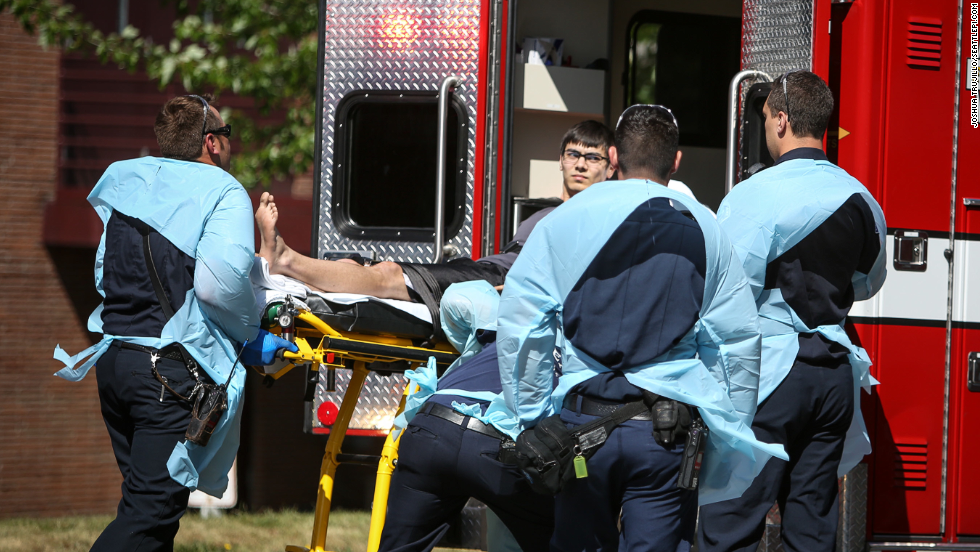 Jon Meis, the student credited with dousing the gunman with pepper spray and tackling him, is loaded into an ambulance after the incident.