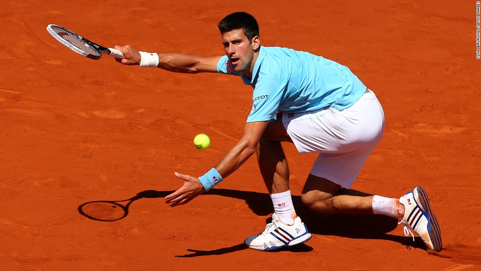 Novak Djokovic stoops to conquer during his French Open semifinal match against Ernests Gulbis of Latvia.