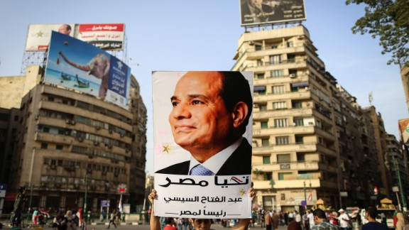 An Egyptian man holds up a portrait of ex-army chief Abdel Fattah al-Sisi as he celebrates in Cairo