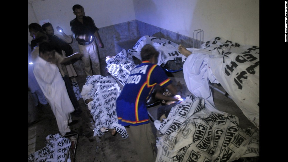 Police examine bodies of security personnel at a Karachi hospital on June 9.