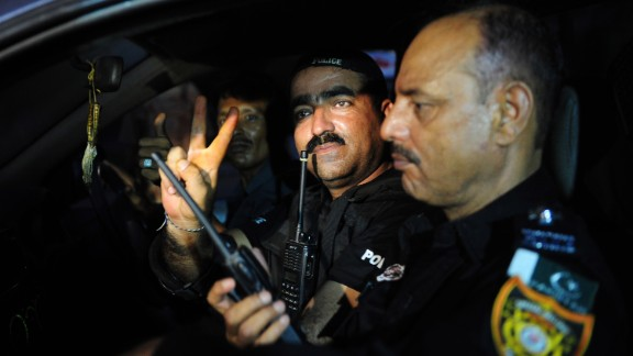 A police commando gives a victory sign June 9 after returning from an operation against militants at the Karachi airport.