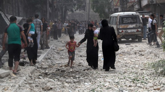 People make their way amid rubble in a street after a reported barrel bombing by government forces in June 2014 in Aleppo's Kallaseh district.