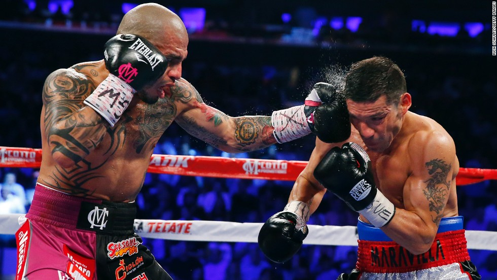 Miguel Cotto lands a left punch to the head of Sergio Martinez during the third round of their WBC middleweight title fight Saturday, June 7, in New York. Cotto stopped Martinez in the ninth round to become the first Puerto Rican boxer to win world championships in four different weight classes.