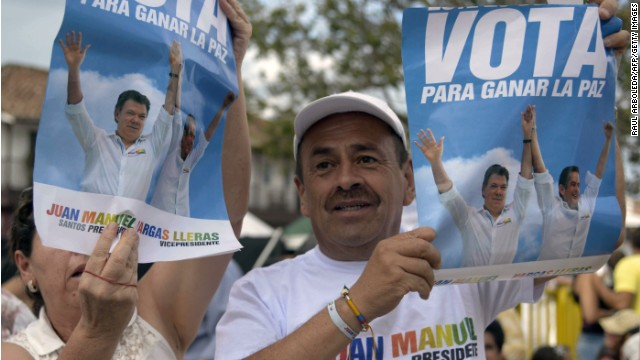 People hold posters with the image of Colombia's President and presidential candidate Juan Manuel Santos during the closing of his campaign in Rionegro, Antioquia department, Colombia, on June 8, 2014. Santos will run against the candidate of the Democratic Center party Oscar Ivan Zuluaga in the presidential run-off on June 15.