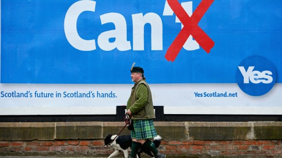 Colin MacDonald Provan walks his dog Colleen down Glasgow High Street past a Yes referendum campaign billboard On May 20, 2014 in Glasgow, Scotland.