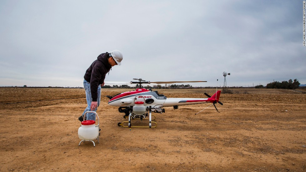 A Researcher At The University Of California Davis Removes Sprayer Containers From Drone