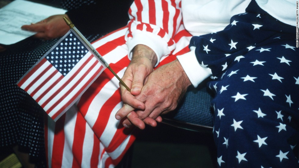 A person holds an American flag during a naturalization ceremony in Los Angeles in 1995.