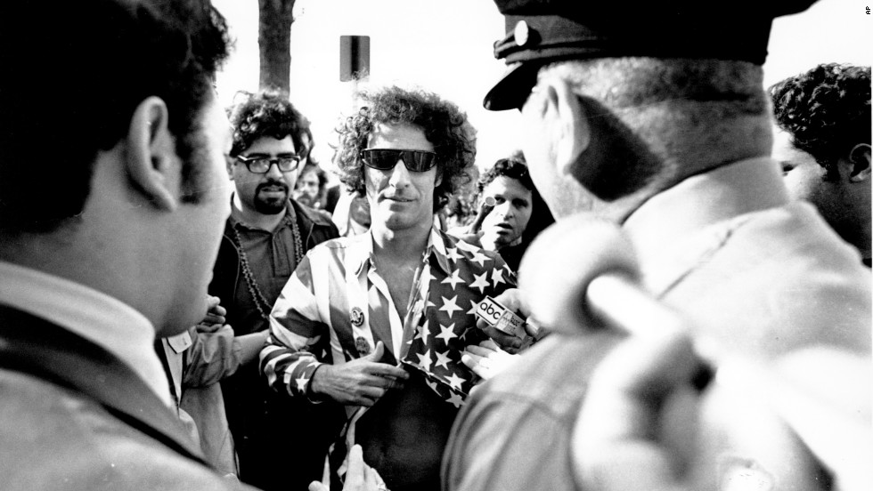 Activist Abbie Hoffman wears an American flag shirt as he is stopped by police on the U.S. Capitol grounds in 1968.
