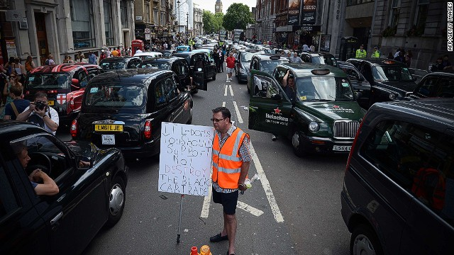 A demonstrator holds a placard as parked taxis block a street in central London during a protest by London black cab drivers against a new private taxi service 'Uber', a mobile phone app, on June 11, 2014. Taxi drivers brought parts of London, Paris and other European cities to a standstill on June 11 as they protested against new private cab apps such as Uber which have shaken up the industry. Thousands of London's iconic black cabs, many of them beeping their horns, filled the roads around Buckingham Palace, Trafalgar Square and the Houses of Parliament to the exclusion of any other vehicles. AFP PHOTO / CARL COURTCARL COURT/AFP/Getty Images
