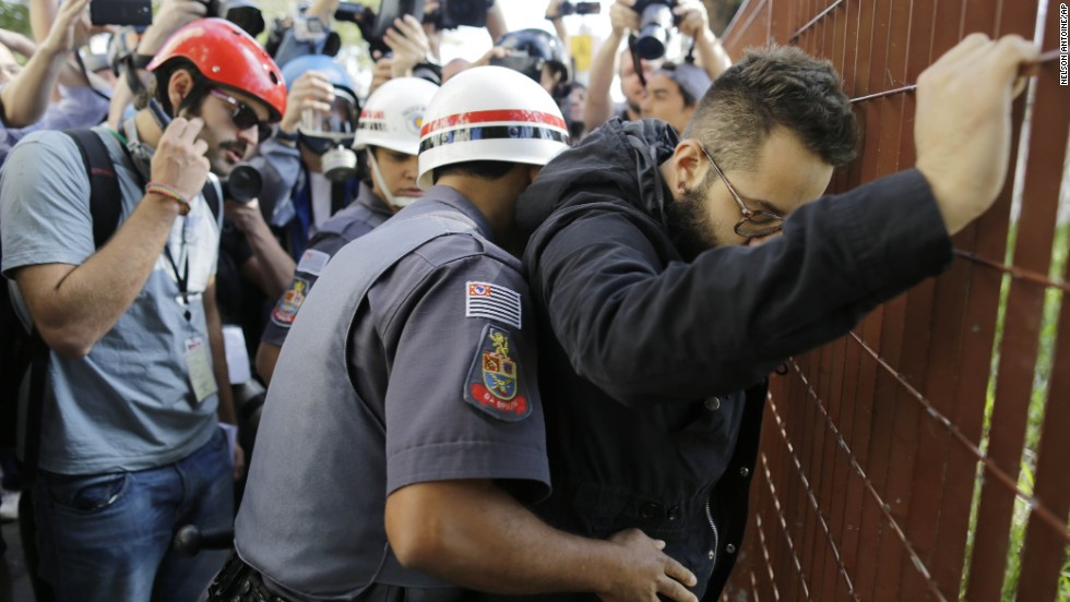 A police officer searches a protester in Sao Paulo.