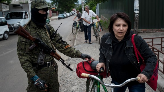 A pro-Russian fighter in Slovyansk checks a woman