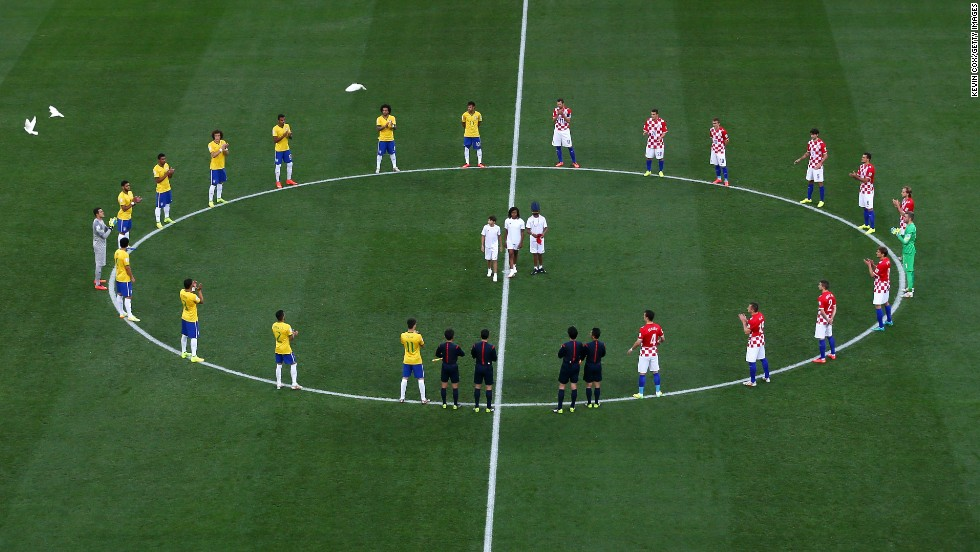 Brazil and Croatia players stand around the center circle as doves are released before the beginning of the match.
