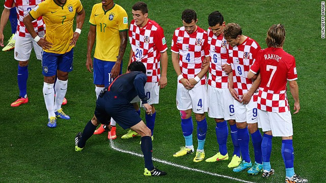 A referee sprays a temporary line on the field during Thursday's opening World Cup match between Brazil and Croatia.