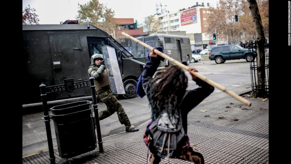 A student in Santiago, Chile, clashes with riot police Tuesday, June 10, during an anti-government protest demanding changes in the state education system.