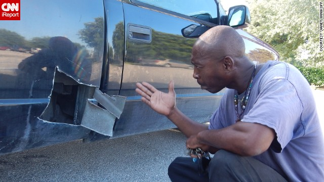 Errand Frazier shows where he cut open his pickup truck to rescue a kitten.