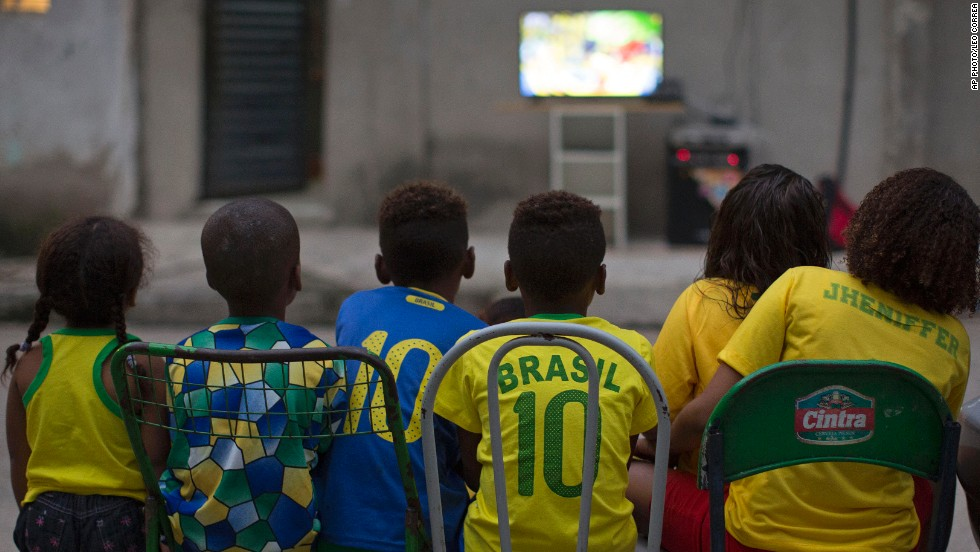 "JUNE 13 - RIO DE JANEIRO, BRAZIL: Children watch the World Cup opening match between Brazil and Croatia in an alley at the Mangueira slum. Brazil secured a nervy 3-1 win. But thousands took to the streets in <a href=""http://edition.cnn.com/2014/06/11/world/americas/brazil-world-cup-tent-city/"">protest against the government for spending $11 billion </a>on the tournament instead of housing, hospitals and schools."